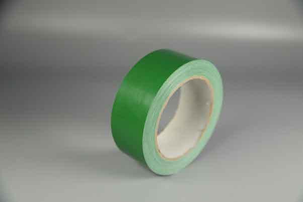 单卷绿色的布基胶带摆放在灰色的布上